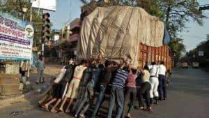 Men pushing overloaded truck